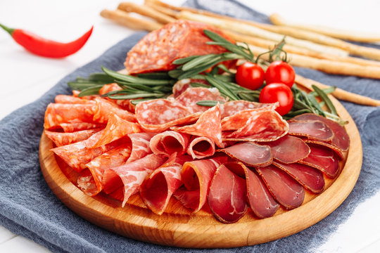 Salami Meat Board Platter Dried Slice Selection Side View. Breadsticks, Ham, Prosciutto and Chorizo Spain Starter Snack Appetizer. Charcuterie Dried Delicatessen for Traditional Spanish Party