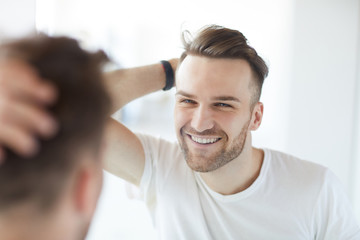 Portrait of handsome young man with lush hair and short stubble looking at his reflection in mirror and smiling, copy space