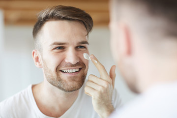 Head and shoulders portrait of handsome young man applying face cream  looking at his reflection in mirror, copy space