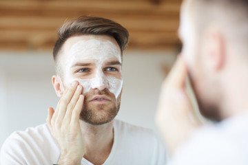 Head and shoulders portrait of handsome young man applying face mask  looking at his reflection in mirror, copy space