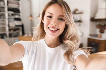 Image closeup of attractive blond woman looking at camera and taking selfie photo in living room