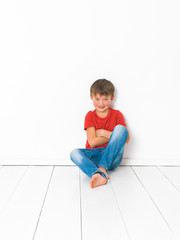 cute and blond boy with red shirt and blue jeans is posing on white wooden floor in front of white background