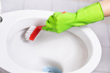 Woman cleans a bathroom toilet with a scrub brush