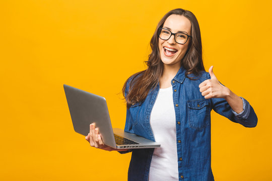Portrait of a smiling young beautiful girl holding laptop computer and showing thumbs up isolated over yellow background.