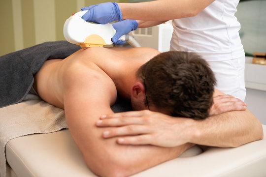 Man in beauty spa - laser epilation