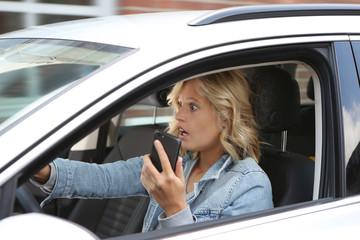 Frau hält während des Autofahrens ein Handy in der Hand und schaut entsetzt