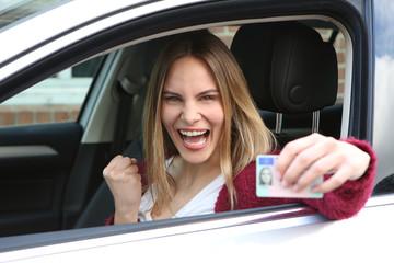 Junge Frau freut sich über ihren Führerschein