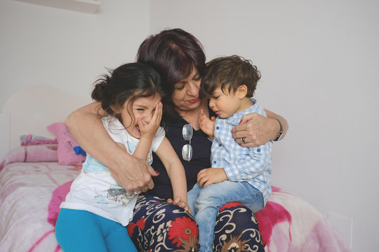 grandmother comforts nietos who are crying with a hug