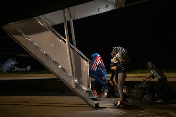 A child from Honduras, draped in a covering with an image of the American flag, walks ahead of his mother towards a plane