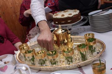 sirviendo té con menta típico marroquí en tetera dorada festiva.-Imagen