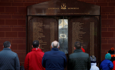 People pay their respects at the Hillsborough Memorial on the 30th anniversary of the Hillsborough disaster when 96 Liverpool supporters were crushed to death at the 1989 FA Cup semi-final football match between Liverpool and Nottingham Forest, outside Liv