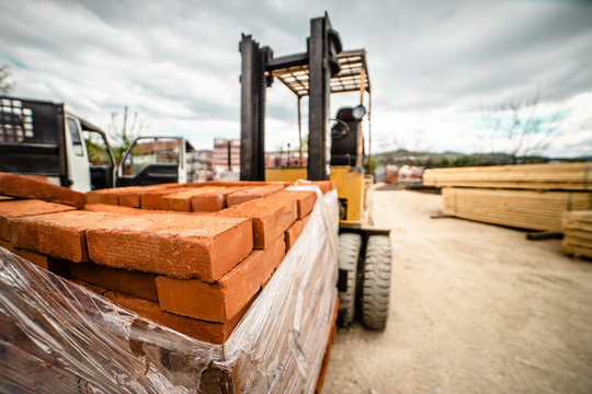 Fork lifter carry construction material clay bricks at the warehouse building site