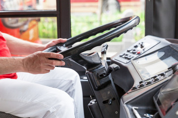 Bus driver at work, holding steering wheel