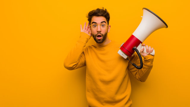 Young man holding a megaphone try to listening a gossip