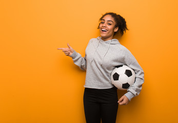 Young fitness black woman pointing to the side with finger. Holding a soccer ball.