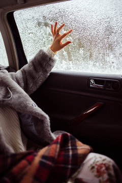 Female hand draws on a snow-covered window.