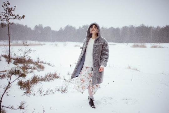 a woman walks near a snowy lake in winter