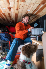 Bearded man cooking on a stove inside of van with puppy after skiing.