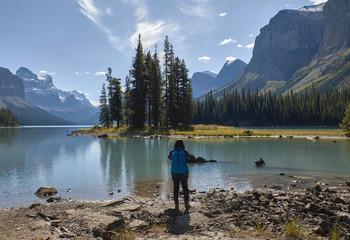 Woman taking pictures in Maligne Lake, Jasper, Alberta, Canada