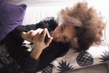 Girl lying on sofa using smartphone