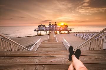 Fototapete - Young man sitting on wooden pier enjoying sunrise at Seebrucke Sellin, Baltic Sea, Germany