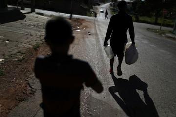 Venezuelans Hildemaro Ortiz and Erasmo Valderrama walk to collect water in the border city of Pacaraima