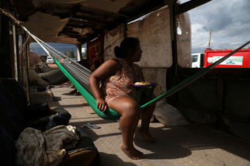 Venezuelan Belki Contreras eats while sitting on a hammock inside of an abandoned bus in the border city of Pacaraima