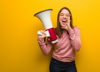 Young cute woman holding a megaphone shouting something happy to the front