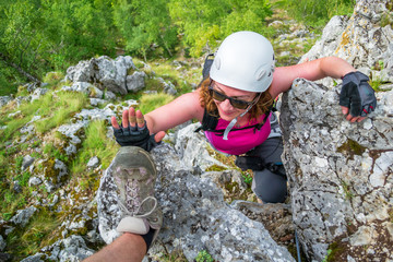 Happy young woman on a via ferrata route at Baia de Fier, Gorj, Romania, near Women's Cave (Pestera Muierilor). Female climber, equipped with gloves, does a high five with another person's shoe.