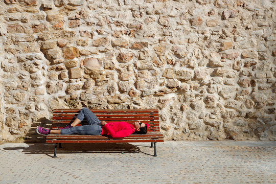 A female runner rests on a bench in the medeival old town section of Cuenca, Spain. The area is a UNESCO World Heritage Site and popular tourist destination.