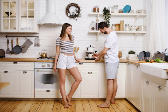 Happy couple woman and man making coffee with machine at their kitchen in new home. Having fun together and cooking breakfast. Happy young family concept