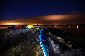 Low level clouds glow orange with light pollution underneath a starry  night sky at a picturesque peninsula campsite in the south cove of Jones Island during a 3-day sea kayaking trip in the San Juan Isands of northwest Washington State. The island is a 188 acre State Park that is only accessible by boat and has 24 campsites.