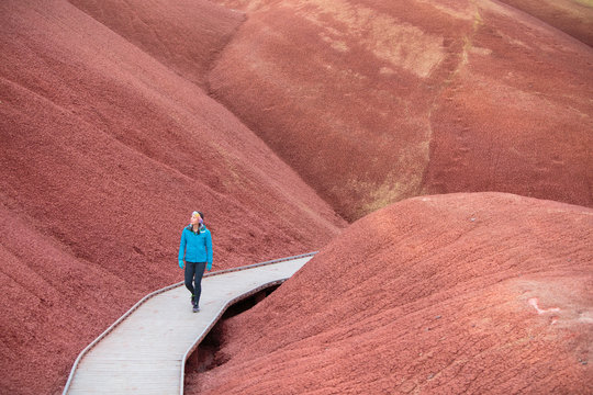 Woman hiking along Painted Cove Trail in Painted Hills Unit, USA