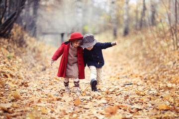 boy and girl in hats walk in park, autumn mood