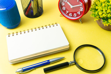 conceptual image. paper note writing with alarm clock, vase, stationery, pen, magnifying glass and portable mini loud speaker against background. Flat lay