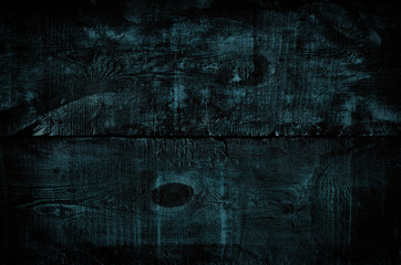 Black tinted wood texture, top view of dark wooden table. Colored blue rustic wall background, texture of old top table, grunge gloomy background