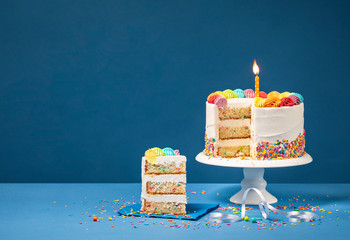 Colorful Birthday Cake with Slice and Sprinkles on Blue