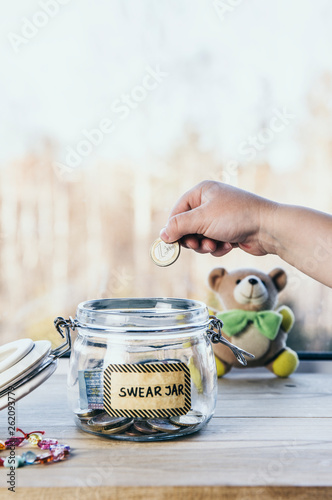 Selective focus on child hand, put euro coin in swear jar