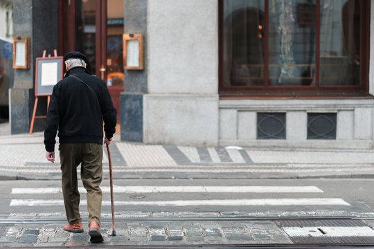 An elderly male with a walking stick slowly walks across a crosswalk in the middle of a city alone