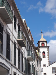 street of old white painted houses and the tower of the historic parish church of saint peters in funchal madeira famous for being the area where cristiano ronaldo was born