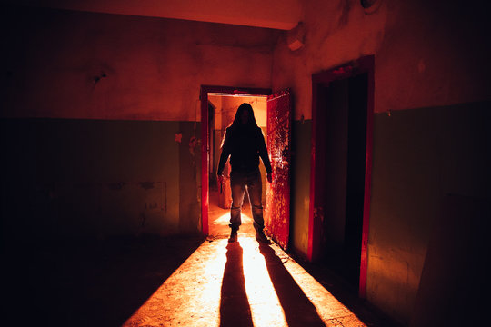 Creepy silhouette with knife in the dark red illuminated abandoned building. Horror about maniac concept