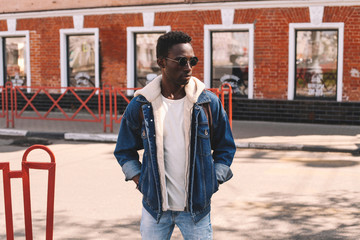 Wall Mural - Stylish african man wearing jeans jacket standing on evening city street