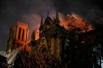 Sparks fill the air as Paris Fire brigade members spray water to extinguish flames as the Notre Dame Cathedral burns in Paris