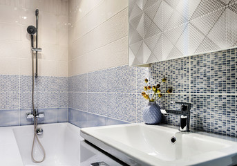Small bathroom in beige and blue tones, the walls are tiled.