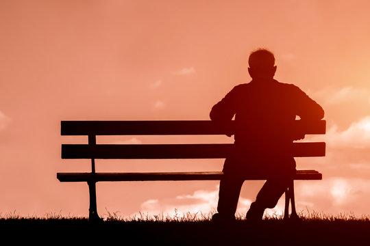 old man sitting alone on park bench under tree;
