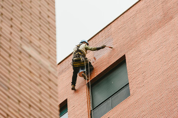 Painter perched hanging on the walls of a building with ropes.
