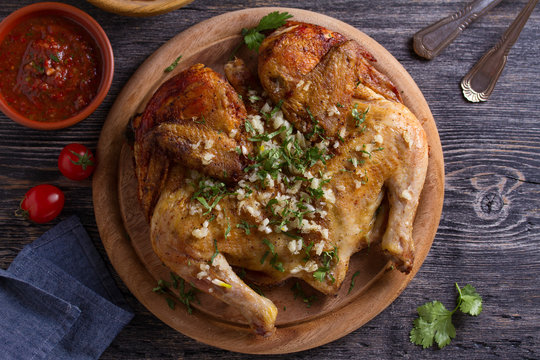 Roasted chicken with garlic on wooden tray. View from above, top