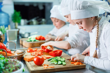 Children grind vegetables in the kitchen.