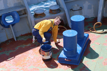Seaman paints a bollard and deck mechanisms on the deck of a ship