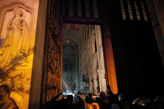 General view from the entrance shows smoke rising around the altar in front of the cross inside the Notre Dame Cathedral as a fire continues to burn in Paris